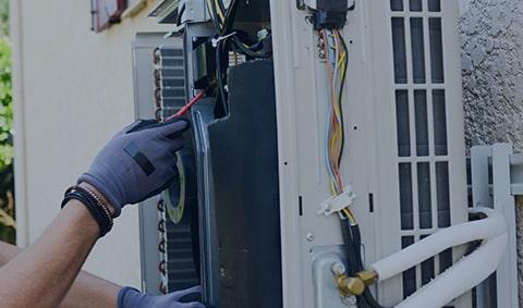 A service technician working on an AC unit
